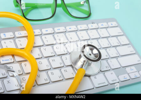 Closeup of a yellow stethoscope lying on notebook keyboard and green glasses. selective focus. - Stock Photo