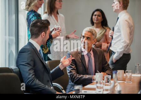 Two male businessmen having a conversation while sat at the conference table.