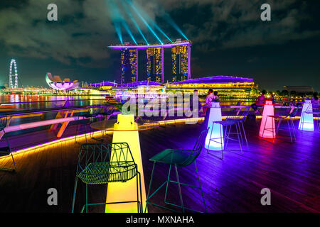 Singapore - April 28, 2018: Marina Bay Sands with colored lights during laser show seen from roof of The Fullerton Pavilion, Italian restaurant Monti At 1-Pavilion in Singapore harbor by night. - Stock Photo