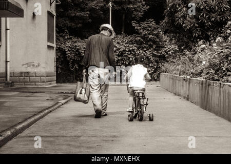 Child is riding on a bicycle in China - Stock Photo