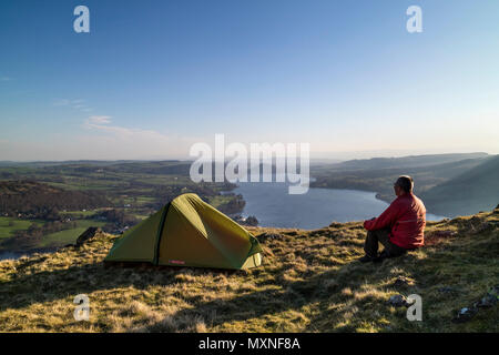 Middle-Aged Backpacker Sitting Outside of Their Tent Enjoying the Early Morning View Over Ullswater from Hallin Fell, Lake District, Cumbria, UK. - Stock Photo