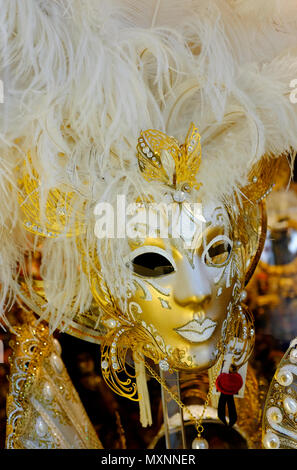 gold venetian carnival masks in shop window, venice, italy - Stock Photo