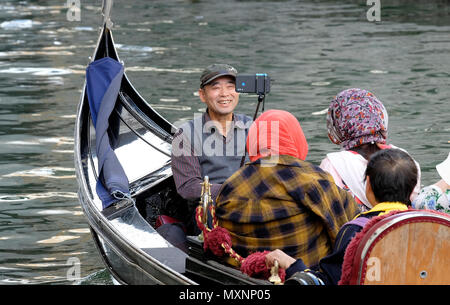 asian man taking selfie picture on gondola in venice, italy - Stock Photo