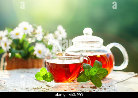 Cup with hot tea with mint and a thyme on a wooden table in a summer garden. - Stock Photo
