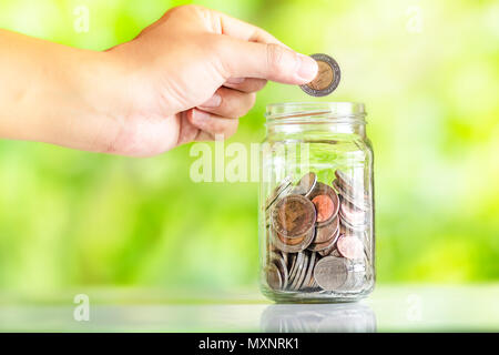 Save money interest Plant Growing In Savings Coins money in the glass saving money with hand putting coins Green Natural background - Stock Photo