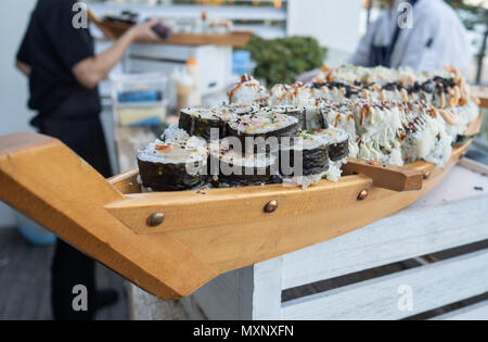 Canapes: assortment of sushi rolls being served on a wooden boat - Stock Photo