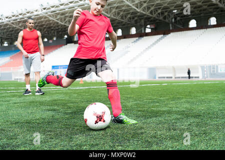 Teenage Boy Kicking Ball - Stock Photo