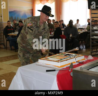 YAVORIV, Ukraine - Lt. Col. Jay Wisham, commander of 6th Squadron, 8th Cavalry Regiment, 2nd Infantry Brigade Combat Team, 3rd Infantry Division cuts a Thanksgiving cake with his cavalry sabre during a Thanksgiving Day celebration here, November 24, 2016. 6­-8 CAV is deployed in support of Joint Multinational Training Group-­Ukraine whose mission focuses on building a sustainable and enduring training capacity and capability within the Ukrainian land forces.  (U.S.Army photo by Spc. John Onuoha / Released) - Stock Photo