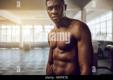 Bare chested man looking tired standing in the gym. Muscular crossfit guy with sweat all over his body after workout. - Stock Photo