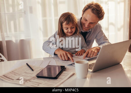 Man sitting with his daughter and looking at a book sitting with laptop computer, tablet and coffee cup on the table. Father spending time with daught - Stock Photo