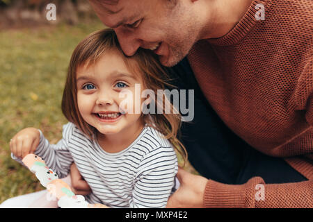 Smiling girl sitting with her father outdoors holding a sugar candy stick. Father and daughter spending time together eating sugar candy. Stock Photo