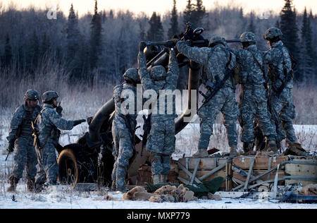 Paratroopers assigned to Alpha Battery, 2nd Battalion, 377th Parachute Field Artillery Regiment, 4th Infantry Brigade Combat Team (Airborne), 25th Infantry Division, U.S. Army Alaska, prepare a M119A2 105mm howitzer for a live fire on Malemute drop zone at Joint Base Elmendorf-Richardson, Alaska, Nov. 22, 2016. USARAK is home to the Army's only Pacific airborne brigade combat team, and maintains the only airborne rapid-response capacity within the Pacific Command Area of Responsibility. (U.S. Air Force photo by Justin Connaher) - Stock Photo