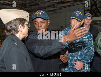 161129-N-TH560-189 SASEBO, Japan (Nov. 29, 2016) Petty Officer 2nd Class Dominic Mando (center), well deck assistant leading petty officer, describes the amphibious capabilities of Bonhomme Richard to Chief of Chaplains Rear Adm. Margaret Kibben in the well deck of amphibious assault ship USS Bonhomme Richard (LHD 6).  Bonhomme Richard, forward-deployed to Sasebo, Japan, is serving forward to provide a rapid-response capability in the event of a regional contingency or natural disaster. (U.S. Navy photo by Petty Officer 3rd Class Jeanette Mullinax/Released) - Stock Photo