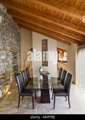 dining room interior in the foreground the glass dining table with brown leather chairs the floor and the wall are made of stone while the ceiling is  - Stock Photo