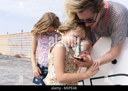 mother showing her daughter something on her mobile phone with the other daughter in the background - Stock Photo