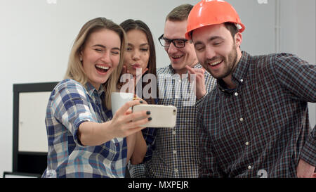 Group selfie shot of colleagues having fun in their office - Stock Photo