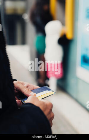 closeup of a young caucasian man on the street, with his wallet in his hands, about to withdraw money from an ATM - Stock Photo
