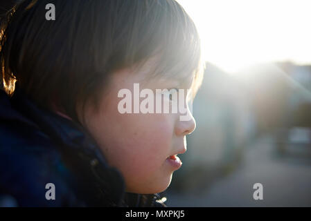 Side profile view of a young preteen Japanese boy in autums sunshine at a school playground - Stock Photo