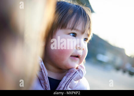 Portrait of a cute young Japanese baby girl on a playground with rosey cheeks from the cold weather - Stock Photo