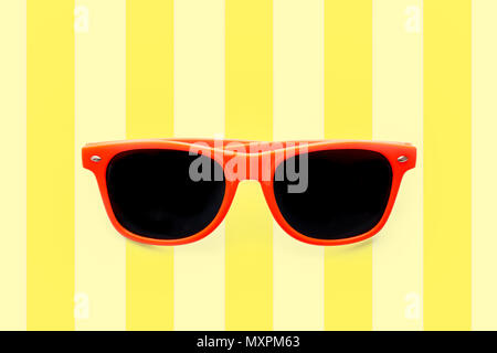 Summer orange sunglasses isolated in striped pastel yellow background. Minimal concept image for sun protection, hot days, tropical travel, summer vac - Stock Photo