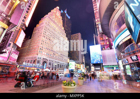 NEW YORK, USA - APRIL 12: The architecture of the famous Times Square in New York city, USA with its neon lights and panels at night and a lot of tour - Stock Photo