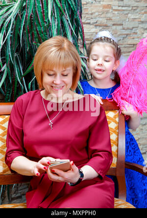 Studio shooting family. Little daughter watching her mother writes something on the phone. - Stock Photo