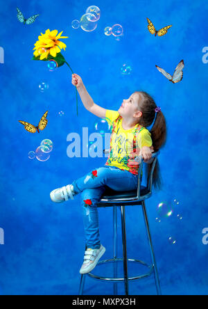 Studio shooting. A girl with a sunflower in her hand on a blue background catches butterflies and soap bubbles. - Stock Photo