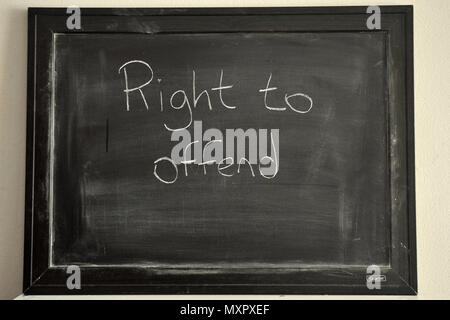 Right to offend written in white chalk on a blackboard - Stock Photo