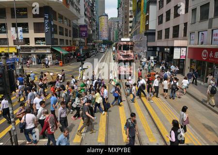 Hong Kong. Crowd walking on a crosswalk in Tsing King Road, Tsing Yi.  JP Books bookshop - Stock Photo