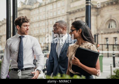 Side view of three business people walking towards the front of a hotel for a business meeting. - Stock Photo