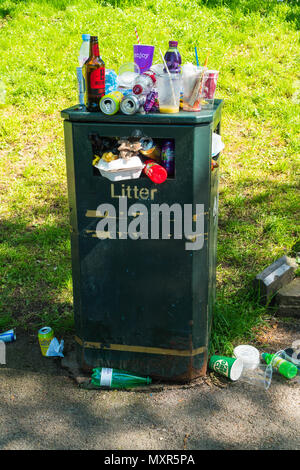 Overflowing waste bin with drinks containers on ground and covering top of bin. Hereford UK - Stock Photo
