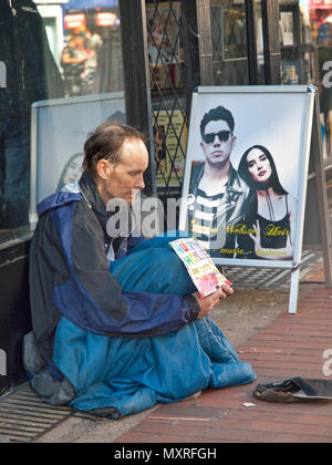 A beggar sits on the pavement in Brighton - Stock Photo