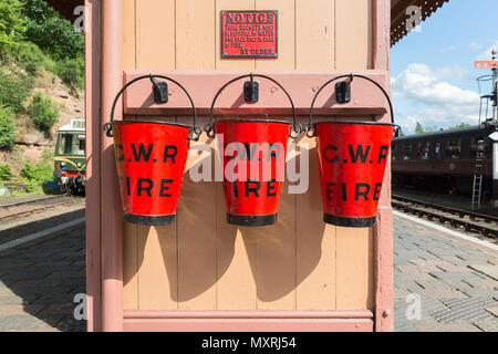 Three red GWR fire buckets, hanging in a row on hooks, displayed on platform at a heritage railway station. Vintage bucket trio on display in the sun. - Stock Photo