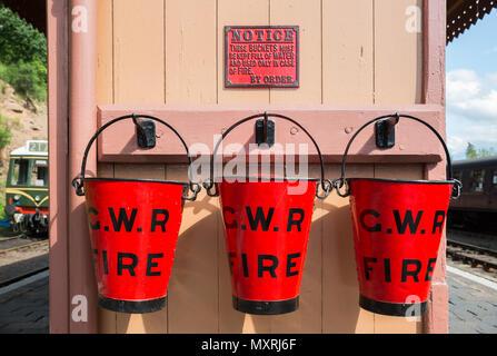 Close up of three red GWR emergency fire buckets on platform at vintage steam railway station. Three red buckets in a row. Trio of buckets in the sun.