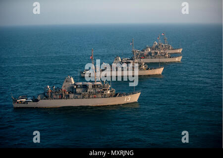 161206-N-ZV163-0371 ARABIAN GULF (Dec. 6, 2016) The Avenger class mine countermeasure (MCM) ships USS Dextrous (MCM 13), USS Gladiator (MCM 11), USS Devastator (MCM 6), and USS Sentry (MCM 3), part of Commander, Task Force (CTF) 52, sail in formation as part of a photo exercise in the Arabian Gulf, Dec. 6, 2016. The combined MCM force enhances mine-hunting capabilities in searching, identifying and neutralizing mines threatening the freedom of navigation and the free flow of commerce. (U.S. Navy photo by Petty Officer 2nd Class Christina Brewer) - Stock Photo