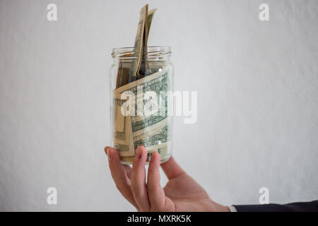 A businessman holds in his hands a bag full of money, savings, savings, dollars in a jar - Stock Photo