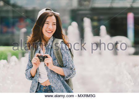 Young beautiful Asian backpack traveler woman using digital compact camera and smile, looking at copy space. Journey trip lifestyle, travel concept - Stock Photo