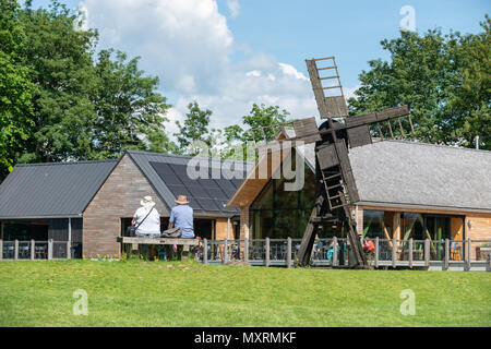People sat on a bench next to a small windmill at the Weald & Downland Living Museum at Singleton, West Sussex, UK. - Stock Photo