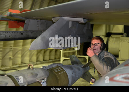 Staff Sgt. Kenneth Gullette, 35th Aircraft Maintenance Unit weapons load crew chief, guides a Joint Direct Attack Munition GBU-31 onto the wing of an F-16 Fighting Falcon at Kunsan Air Base, Republic of Korea, Nov. 30, 2016. Members of the 35th AMU safely prepare F-16's for a variety of missions, which feed into the 8th Fighter Wings priorities of defending the base and being postured to respond to any threats. (U.S. Air Force photo by Senior Airman Michael Hunsaker/Released) - Stock Photo