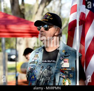 "Army veteran Bill Erickson, holds a flag during the Pearl Harbor Remembrance Day ceremony at Veterans Memorial Park in Tampa, Fla., Dec. 7, 2016. Service members, veterans, retirees and civilians gathered to commemorate the 75th anniversary with a ceremony themed ""We Remember the Fallen."" (U.S. Air Force photo by Senior Airman Vernon L. Fowler Jr.) - Stock Photo"
