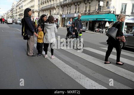 Parents and children going home on an afternoon after the school day walking and on bike near a pedestrian crossing  in Paris France  KATHY DEWITT - Stock Photo
