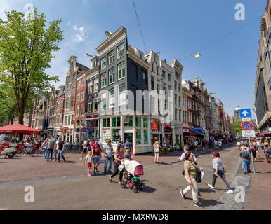 AMSTERDAM, NETHERLANDS - MAY 27: Pedestrians cross over the Damstraat Street among typical canal houses on May 27, 2018 in Amsterdam, Netherlands. Amsterdam's buildings along the canals (called as canal houses) were designed in unique architectural style. - Stock Photo