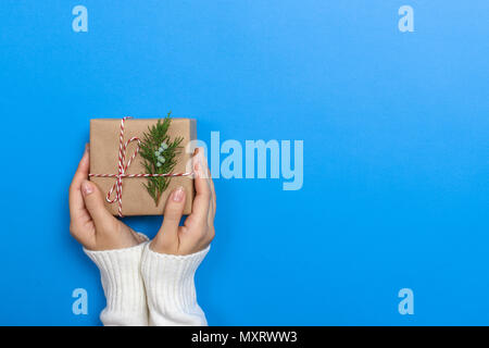Woman hands holding a Christmas gift box. Christmas presents and New Year. Handmade. - Stock Photo