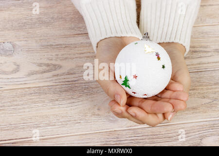Christmas concept with hand and white ball - christmas tree toy. White round christmas ball in female hand. Wooden Background. - Stock Photo