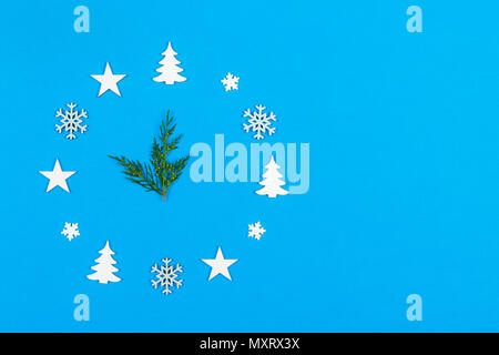 Concept clock made of christmas decoration showing five to midnight New Year on blue background with copy space.