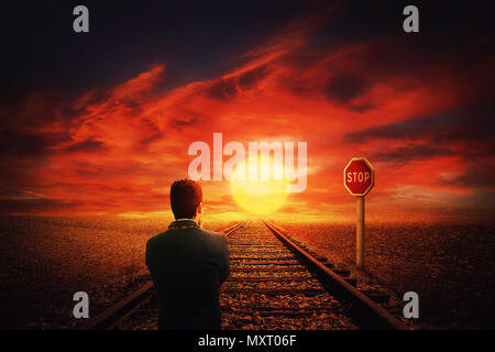 Surreal view as a man walking on a railroad along desert in front of a STOP road sign. Beautiful sunset background and businessman thinking his next m - Stock Photo