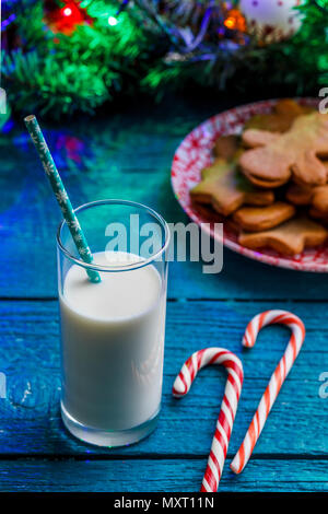 Image of ginger biscuits, glass of milk, caramel sticks, spruce branches with burning garland