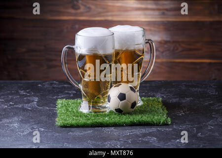 Photo of two beer mugs, green grass with soccer ball - Stock Photo