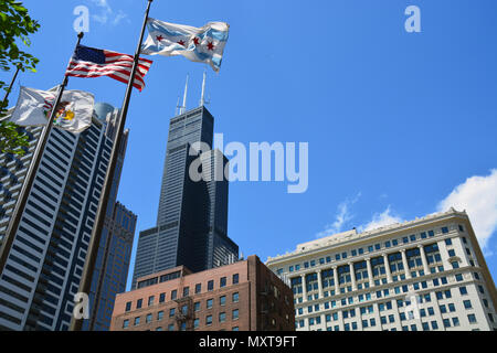 Flags waive in the wind and frame the Willis Tower on a street in Chicago's South Loop. - Stock Photo
