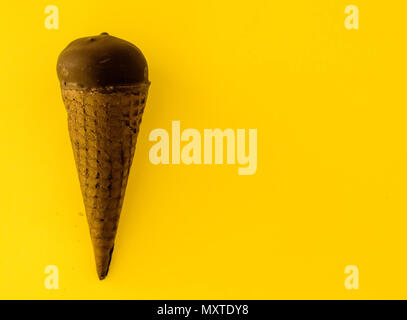 Vanilla ice cream with cranberry jam in a sugar cone dipped in chocolate on yellow background.Pastel colour.Cool off in the hot summer.Copy space righ - Stock Photo